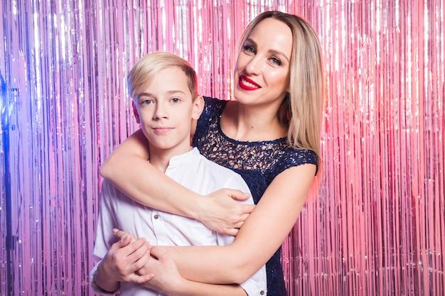 Moedersdag, kinderen en familieconcept - tienerjongen en zijn moeder die op glanzend partijoppervlak omhelzen.