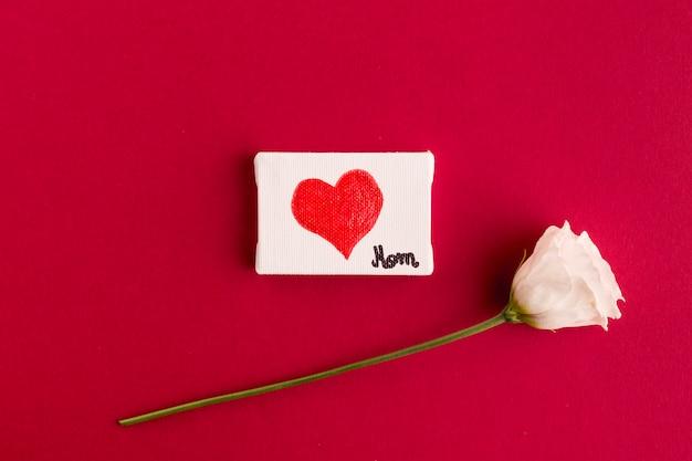 Moedertitel en hart op papier dichtbij bloem