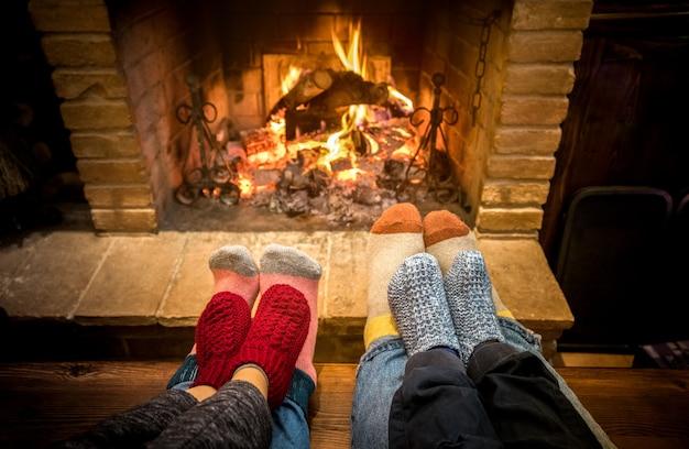 Moedervader en jonge geitjes die bij comfortabele open haard thuis op kerstmistijd zitten