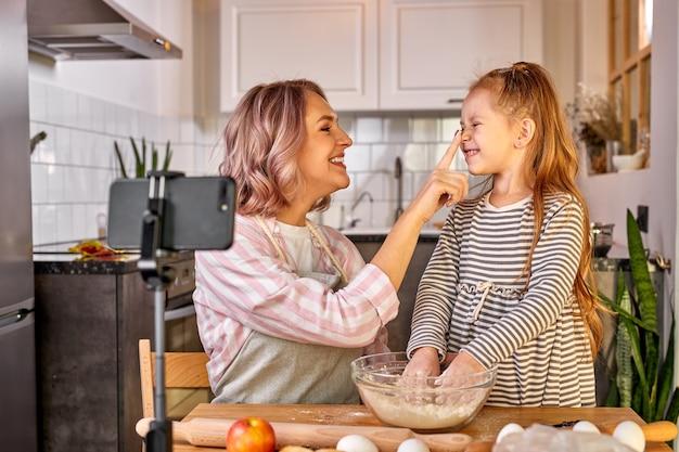 Moedervoedselblogger registreert het proces van koken met dochter op smartphone, ze hebben plezier, praten, genieten van samen eten bereiden