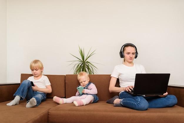 Moederzitting met laptop en het werken terwijl de kinderen telefoon spelen. uitdagingen bij het opvoeden, onverantwoordelijke ouders
