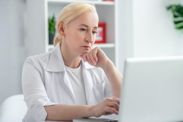 Moeilijk geval. blonde artsenzitting op middelbare leeftijd bij haar bureau en het kijken geconcentreerd