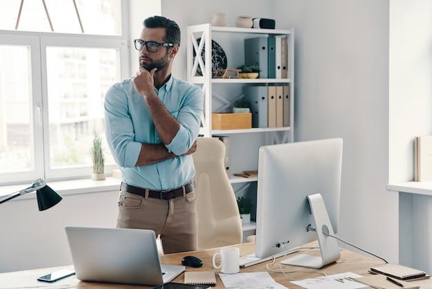 Moeilijke beslissing om te nemen. jonge moderne zakenman die de hand op de kin houdt en wegkijkt terwijl hij op kantoor werkt