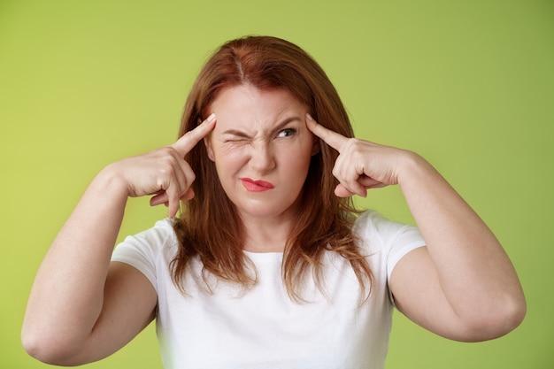Moeilijke beslissing perplex aarzelend roodharige vrouw van middelbare leeftijd probeert puzzel op te lossen kijken verbaasd onrustig grijns sluiten ogen gluren rechts aanraking tempels nadenkend denken intens groen muur