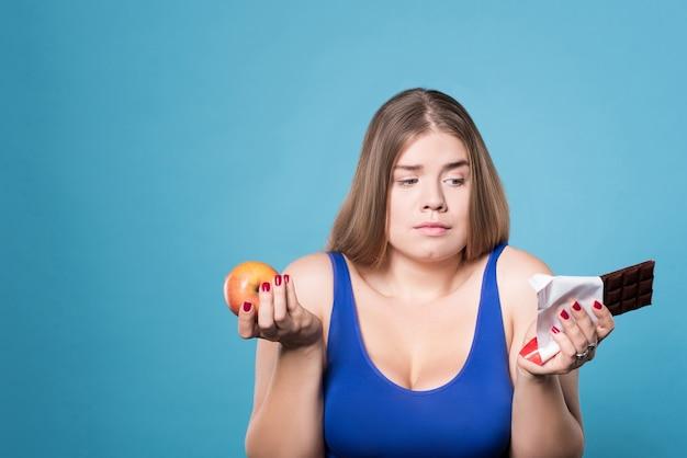 Moeilijke beslissing. portret van de vrij twijfelachtige jonge appel van de vrouwenholding in één hand en chocolade in andere.