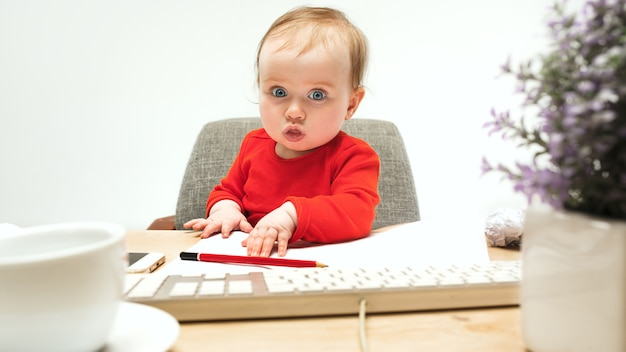 Moeilijke dag. kind babymeisje zit met toetsenbord van moderne computer of laptop in witte studio