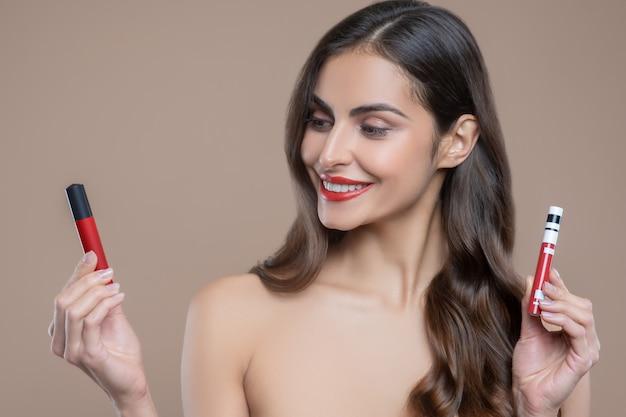 Moeilijke keuze. mooie jonge vrolijke vrouw met blote schouders die met rode lipgloss een van de twee kiezen