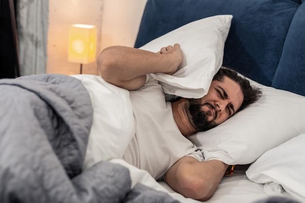Moeilijke maandag. vrolijke ongelukkige man die in bed wil blijven terwijl hij 's ochtends de wekker hoort