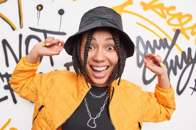 Moeilijke meisjestiener heeft vrolijke uitdrukking danst tegen graffiti op verlaten gebouwmuur verrast heeft brede glimlach in eigen stijl