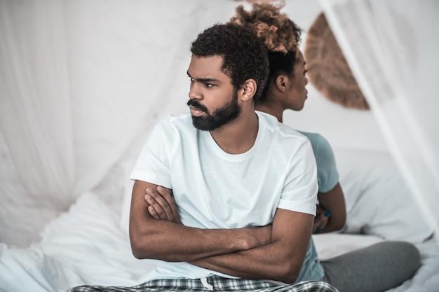 Moeilijke relatie. jonge, bebaarde echtgenoot met een donkere huidskleur in een lichte t-shirt met gevouwen armen en vrouw die tegen elkaar zit