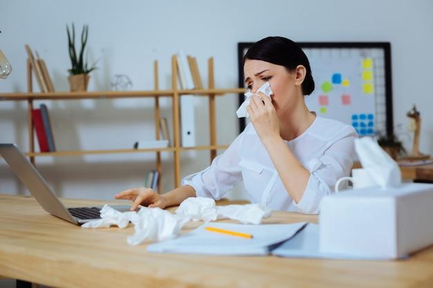 Moeilijke situatie. triest kantoormedewerker die haar neus bedekt en voorhoofd rimpelt tijdens het gebruik van de computer