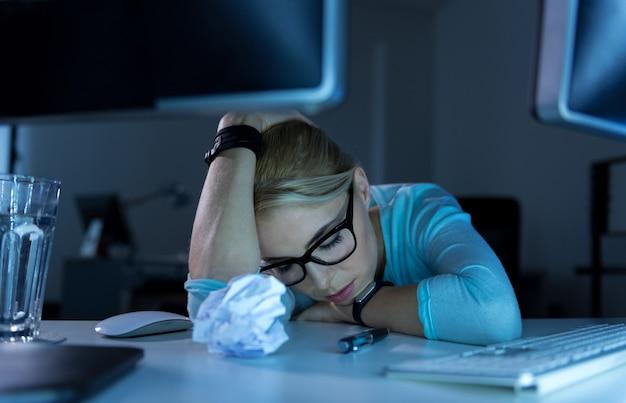 Moeilijke werktijden. boos uitgeput vermoeide techneut die op kantoor zit terwijl hij zich moe voelt en in slaap valt