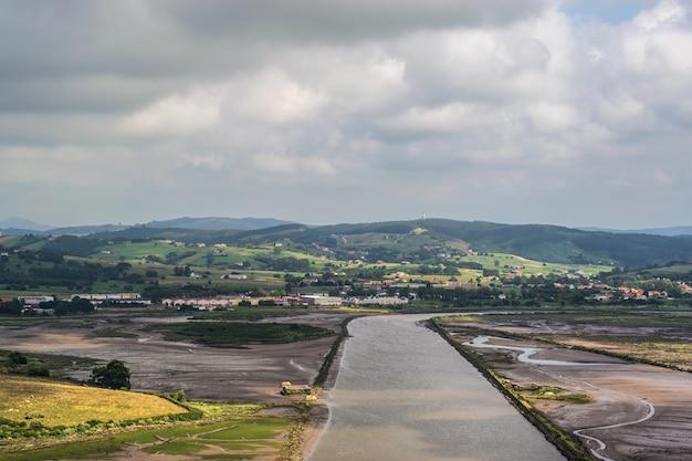 Moerassen van een rivier tussen groene heuvels