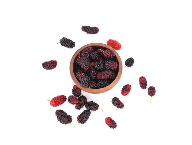 Moerbeifruit en moerbeiboomblad in bruine kom op wit gezond geïsoleerd voedsel van het moerbeifruit