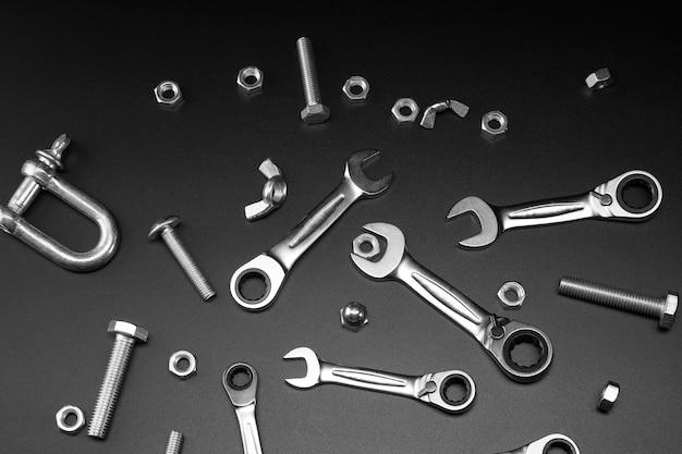 Moeren, bouten, moersleutel, pal op een donkere achtergrond. hulpmiddelen voor het vastmaken van boutverbindingen.