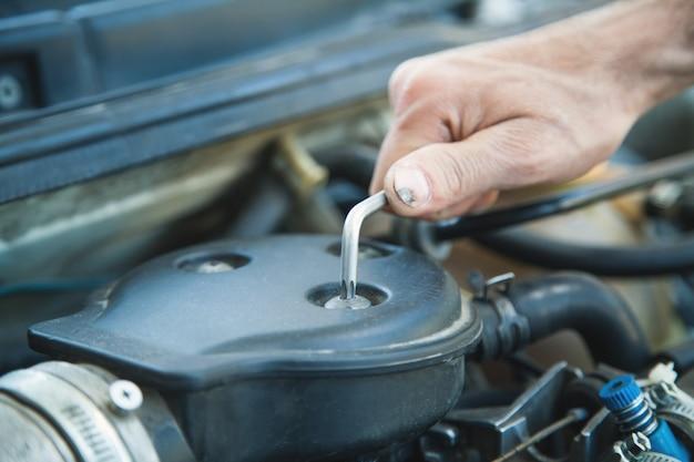 Moersleutel in de hand. man aan het werk in reparatieservice en tot vaststelling van de motor van een auto