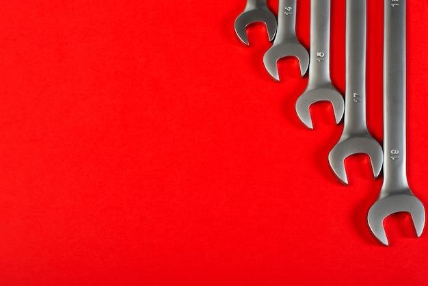 Moersleutels op rood, bovenaanzicht met ruimte voor tekst.