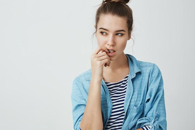 Moet een plan maken. portret van doordachte aantrekkelijke blanke meisje met broodje kapsel opzij kijken terwijl bijten vingernagel, denken aan iets, nerveus.