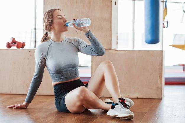 Moet herstellen. sportieve jonge vrouw heeft fitnessdag in de sportschool in de ochtendtijd