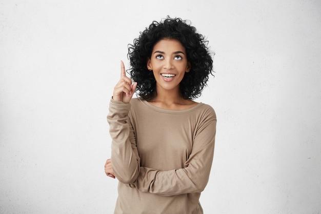 Moet je zien! binnenportret van vrolijk aantrekkelijk terloops gekleed jong wijfje met krullend haar die haar wijsvinger omhoog richten, iets interessants aanwijzend, gelukkig opgewekt kijkend