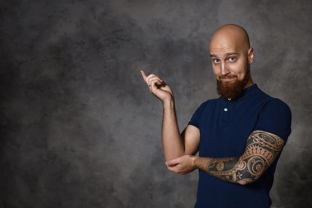 Moet je zien! geïsoleerde grappige kale bebaarde man met tatoeage wijsvinger verhogen en naar de linkerhoek wijzen, opwinding of nieuwsgierigheid uiten, wenkbrauwen optrekken. lichaamstaal
