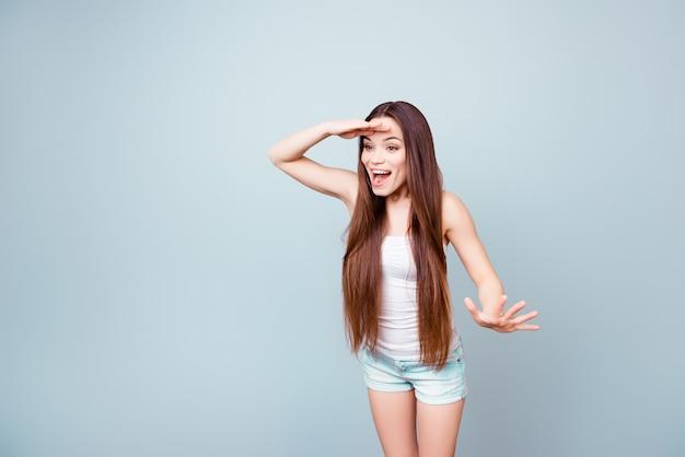 Moet je zien! geschokt jong schattig meisje kijkt ver, verbaasd, in zomeroutfit, staat op een blauwe ruimte, heeft lang gezond donkerbruin haar