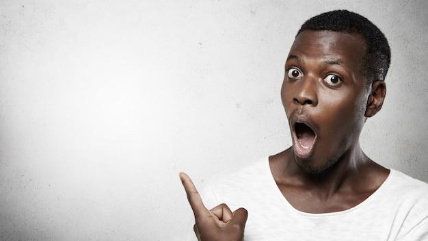 Moet je zien! headshot van een totaal geschokte afrikaanse man met grote ogen, gekleed in een wit t-shirt, zijn mond wijd openend en met zijn vinger wijzend naar de lege muur met kopie ruimte voor uw advertentie-inhoud