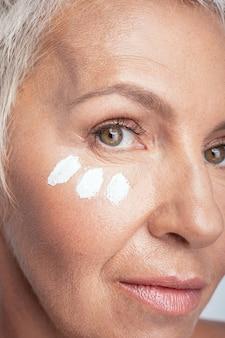 Moet kiezen. attente vrouw die naar de camera staart tijdens het testen van nieuwe cosmetica