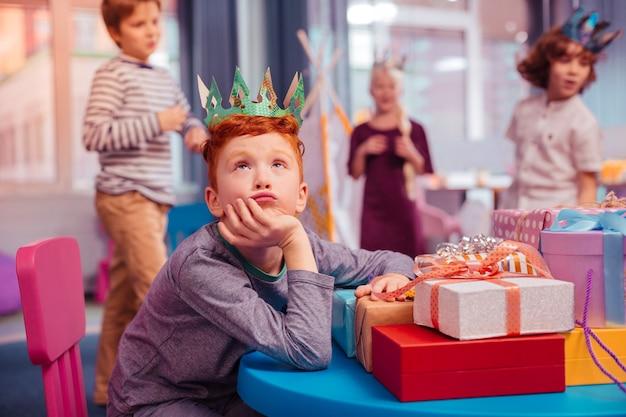 Moet nadenken. vrolijke jongen leunend op tafel terwijl hij zich verveelt tijdens de viering