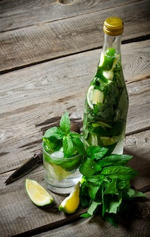 Mojito-cocktail. cocktail in glas en fles, ook munt en limoenen (lemmetjes) op een houten tafel.