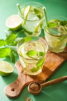 Mojito cocktail en ingrediënten over groene tafel