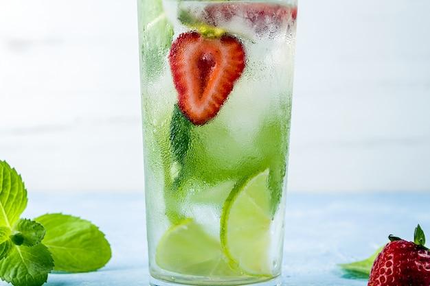 Mojito cocktail met ijsblokjes. glas zomerlimonade of ijsthee. verfrissende koele detoxdrank met aardbei, limoen en munt. gezond eten.