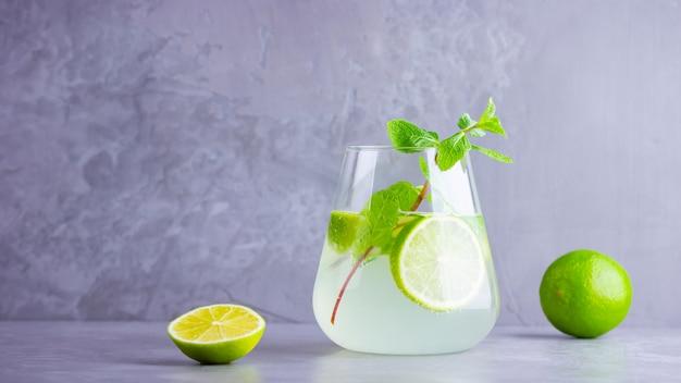Mojito-cocktail met limoen en munt. mojito op een grijze achtergrond. geïnfundeerd water