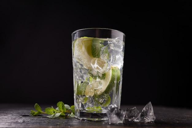 Mojito cocktail met limoen, munt en ijsblokjes geïsoleerd