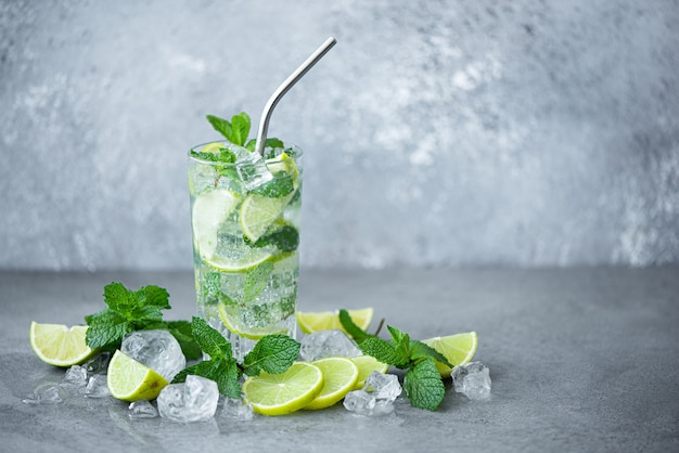 Mojito cocktail met munt, limoen en ijs in een hoog op een grijze achtergrond