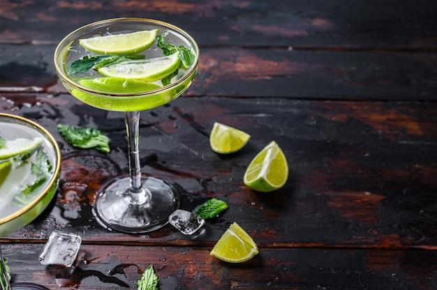 Mojito cocktaildrank met limoen, ijs en munt. zwarte houten achtergrond. bovenaanzicht. kopieer ruimte.