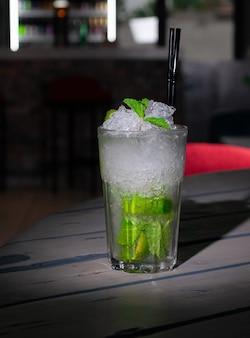 Mojito long drink gedecoreerd met limoen en munt met crushed ijs. in een glazen beker collins. op een grijze houten achtergrond. detailopname. hard licht
