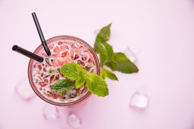 Mojito met aardbeien frambozen en munt op de roze tafel