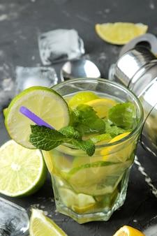 Mojitococktail in een glas met limoen, munt en citroen en baraccessoires op een donkere betonnen ondergrond. maak een mojito.