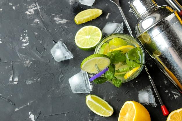 Mojitococktail in een glas met limoen, munt en citroen en baraccessoires op een donkere betonnen ondergrond. mojito koken. bovenaanzicht. vrije plaats