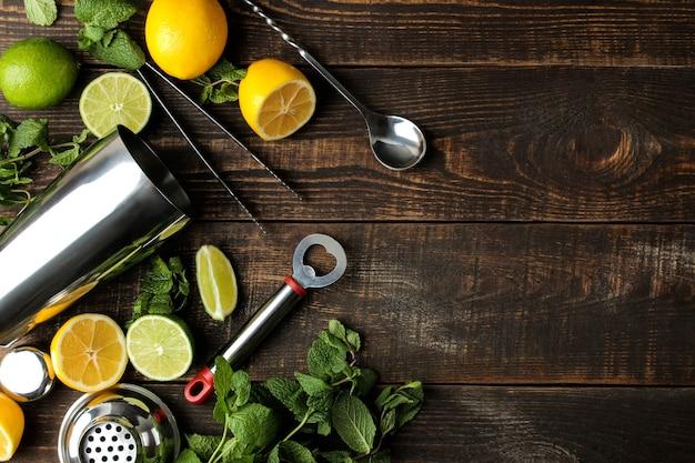 Mojitococktail in een glas met limoen, munt en citroen en baraccessoires op een houten bruine tafel. mojito koken. bovenaanzicht. vrije plaats