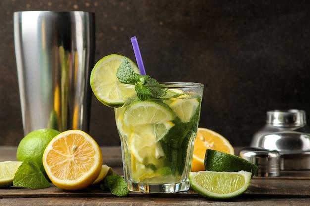 Mojitococktail in een glas met limoen, munt en citroen en baraccessoires op een houten bruine tafel. mojito koken.