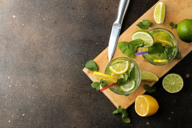 Mojitococktail in een glazen tuimelaar met limoen, munt en citroen en op een donkere betonnen ondergrond. maak een mojito. bovenaanzicht. vrije plaats