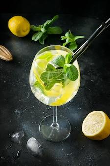 Mojitococktail of limonade met munt in glas op zwarte. detailopname. zomer drankje.