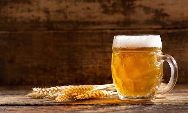 Mok bier met tarwe oren op houten tafel