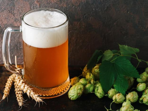 Mok bier op tafel met tarwe en groene hop