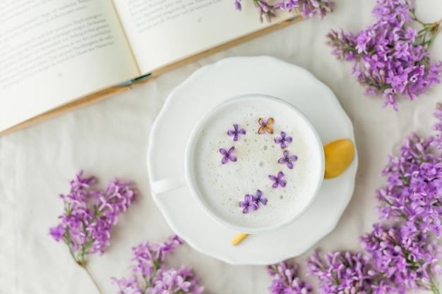 Mok cappuccino op een beige ondergrond. lila bloemen, boek.