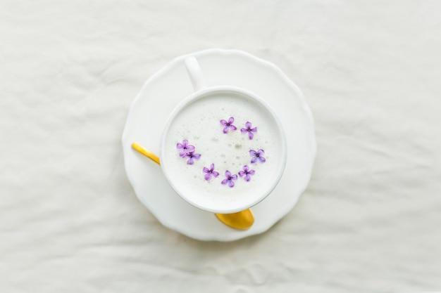 Mok cappuccino op een beige ondergrond. lila bloemen.
