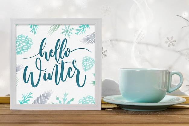 Mok in de buurt van frame met hallo winter titel op houten tafel in de buurt van bank van sneeuw