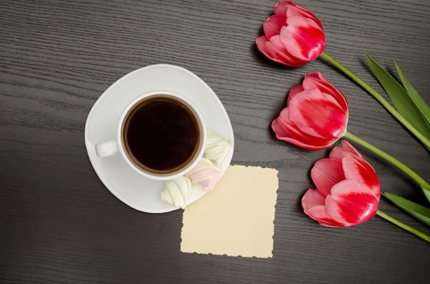 Mok koffie en marshmallows, schone ansichtkaart, drie roze tulpen
